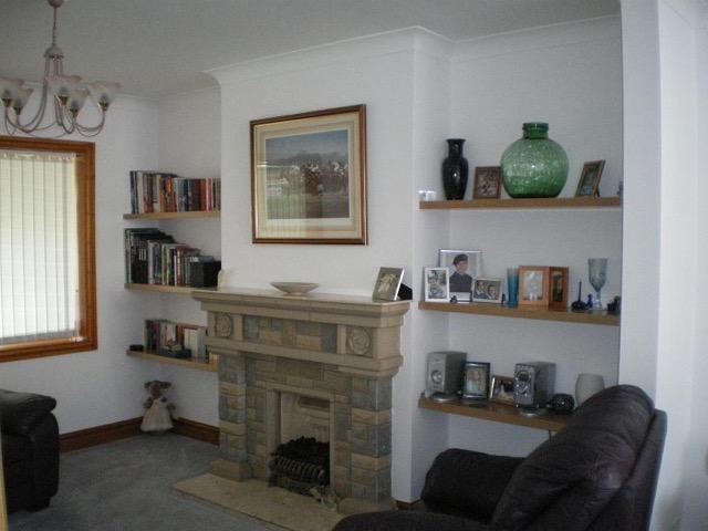 oak floating shelves in both alcoves